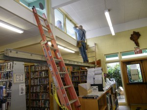 Workers replace windows at the aging Flora M. Laird Public Library in Myrtle Point.  (Courtesy Photo)