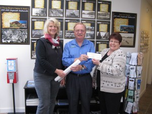 Jacquie Beveridge (L.), Chapter Regent for the Oregon Dunes Chapter of the DAR presents a $5,000 check to Oregon Coast Military Heritage Museum board member Cal Applebee as he, in turn, hands the plans for the OCMHM Remembrance Garden to landscape contractor Lisa Sedlacek of Laurel Bay Gardens.  (Photo by OCMHM)