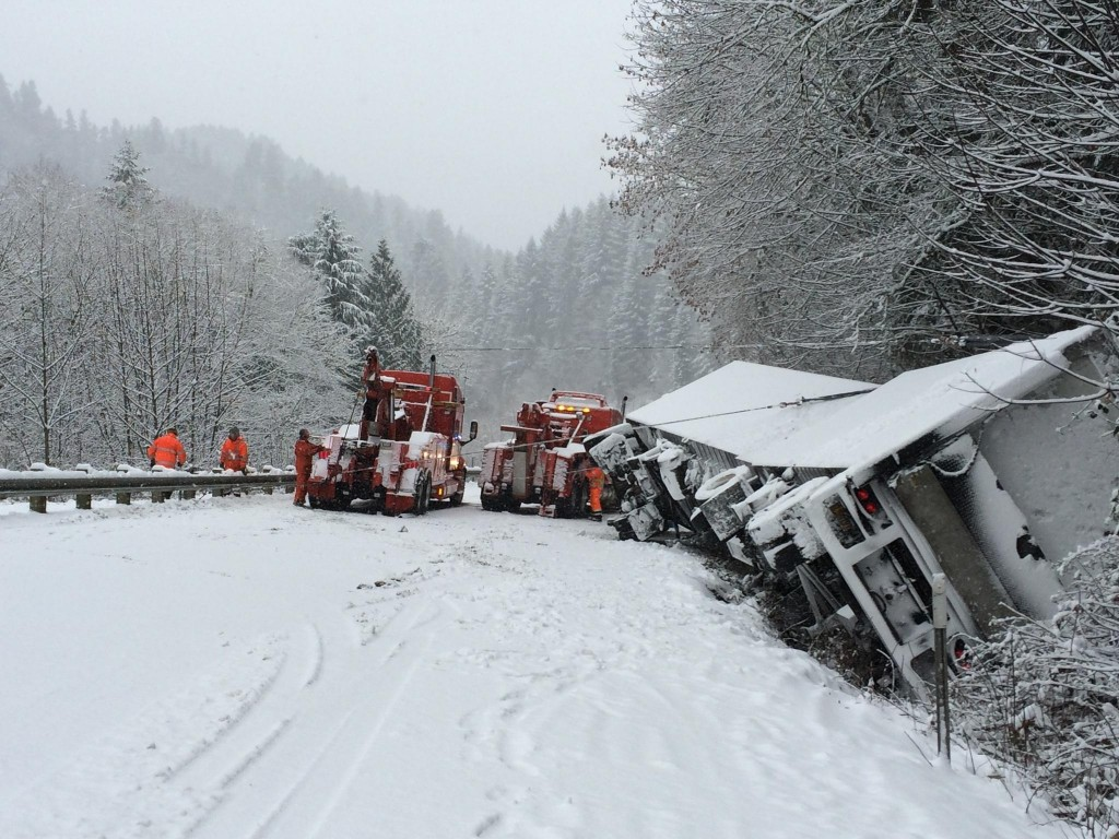 Towing company employees work to remove an overturned semi-truck and trailer at milepost 18.5 on Highway 126, four miles east of Mapleton.  (Oregon Department of Transportation Photo)