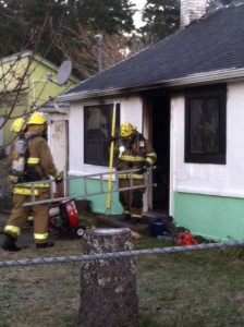 Fire fighters work on mopping up a blaze that gutted a small cottage on Rhododendron Drive near Ivy Street December 5th, 2013.