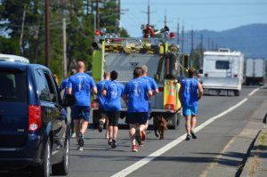 Crew members from U.S. Coast Guard Station Siuslaw River carry the Oregon Special Olympics Torch through Florence Tuesday morning escorted by an engine from Siuslaw Valley Fire and Rescue. (photo by Debra Heldt Cordone)